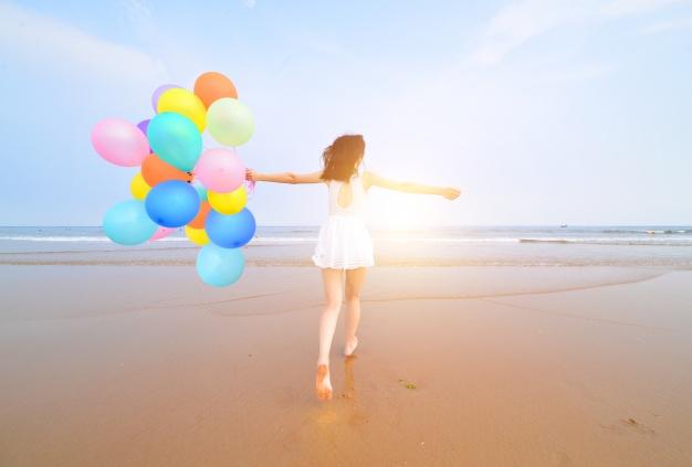 vista-trasera-de-mujer-joven-celebrando-su-cumpleanos-en-la-playa_1112-840