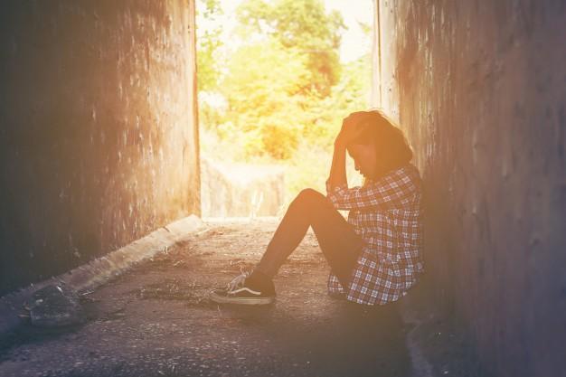 chica-infeliz-sentada-en-el-suelo_1150-425